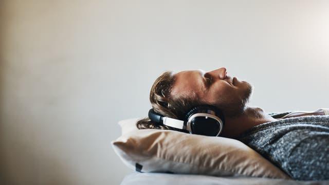 Mann hört Musik im Bett