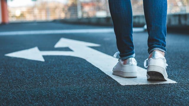 Beiner einer Frau in weißen Turnschuhen auf der Straße auf einem Pfeilzeichen, das sich verzweigt.