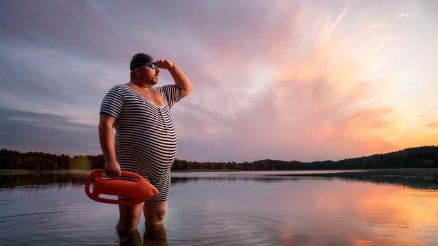 Ein etwas älterer, wohlbeleibter Rettungsschwimmer in gestreiftem Badeanzug steht bei Sonnenuntergang im Wasser eines Sees.