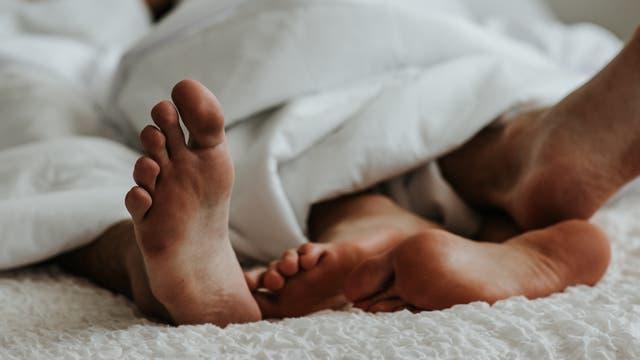 Füße eines Paares unter einer Bettdecke