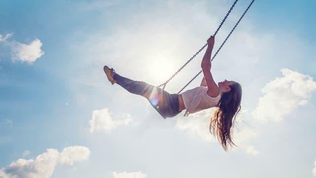 Eine Junge Frau auf einer Schaukel vor blauem Himmel.