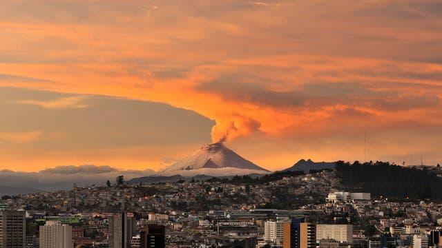 Ausbruch des Vulkans Cotopaxi nahe der Stadt Quito. Im Vordergrund das Stadtzentrum, im Hintergrund ein rauchender Vulkankegel.