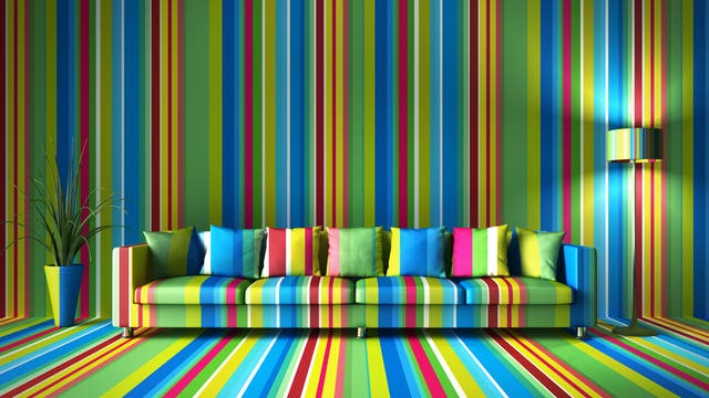Ein bunt gestreiftes Sofa vor einer im gleichen Streifenmuster gestrichenen Wand.