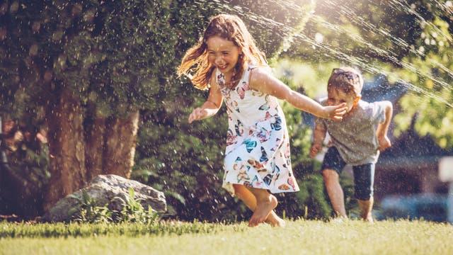 Kinder spielen im Garten mit einem Rasensprenger.