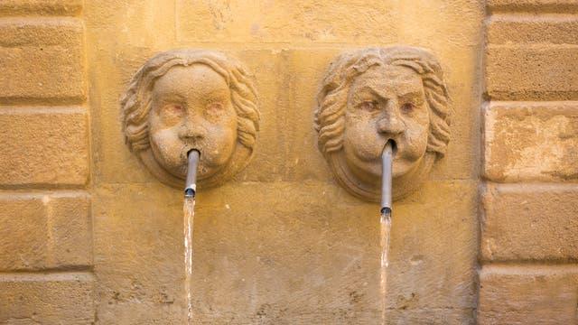 Zwei kuriose gesichtsförmige Wasserspeier speien Wasser.