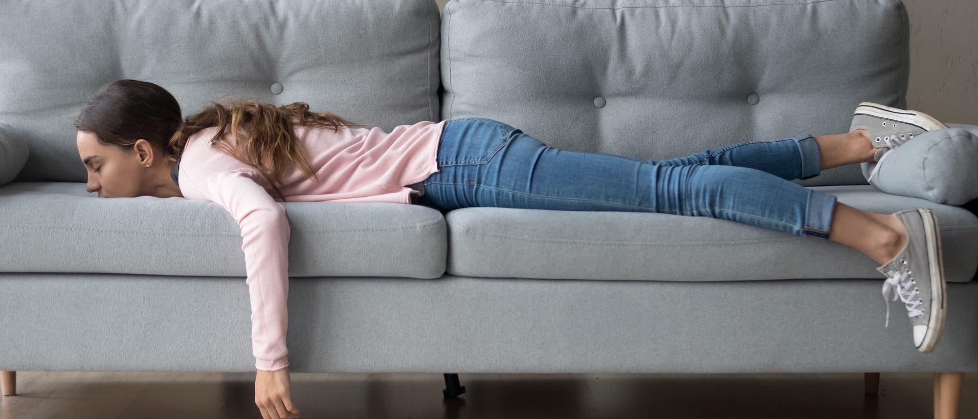 Junge Frau liegt bäuchlings auf dem Sofa und schläft