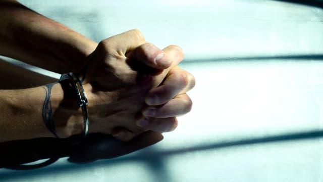 Gefaltete Hände mit Handschellen
