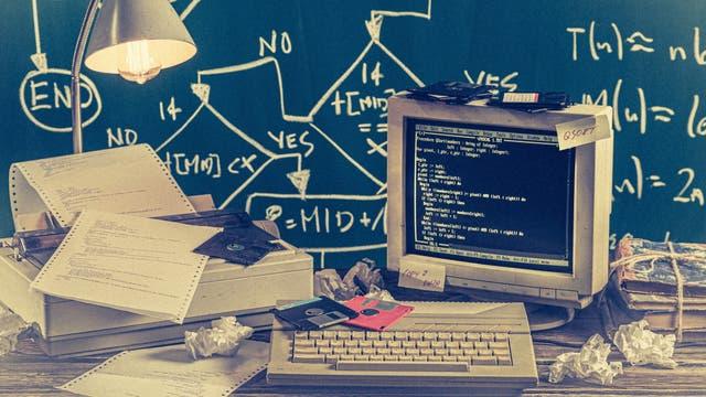 Schreibtisch mit frühem Computer, Disketten und Drucker