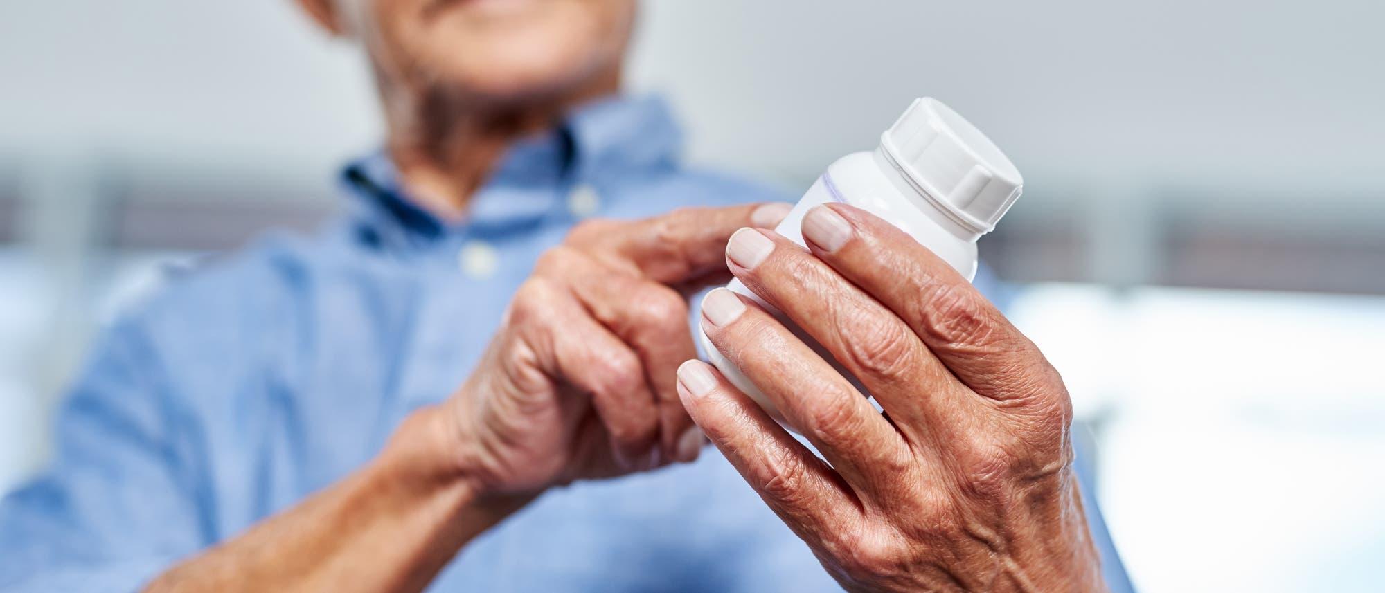 Ein Mann liest die Beschreibung der Inhaltsstoffe eines Medikaments.