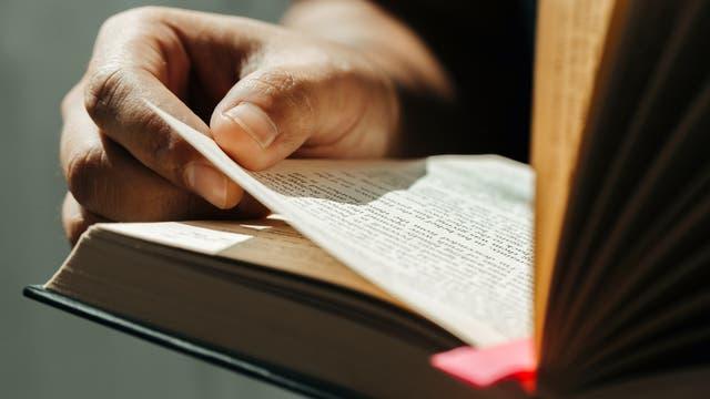 Großaufnahme einer geöffneten Bibel, die in den Händen gehalten wird.