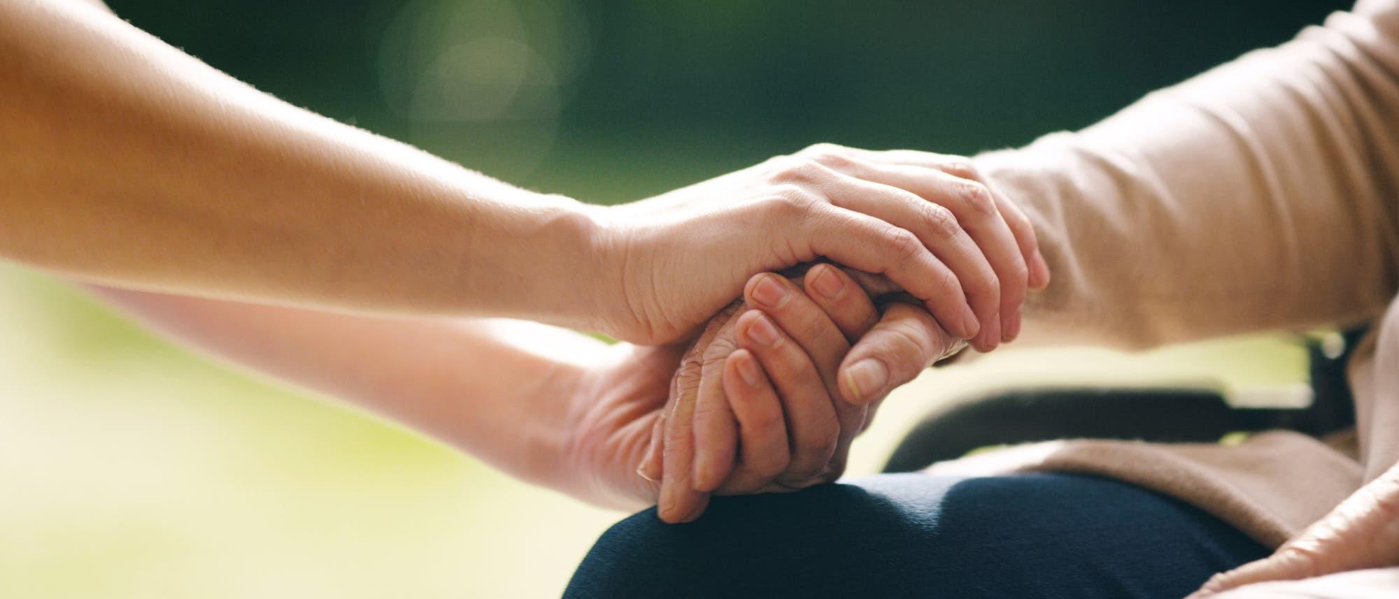 Zwei Hände ergreifen die Hand eines Menschen im Rollstuhl