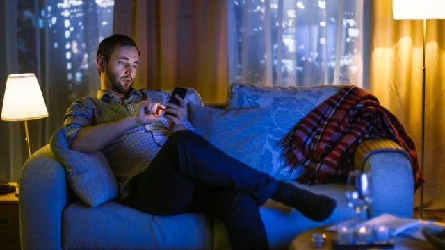Mann sitzt mit Handy auf der Couch, im blauen Licht des Fernsehers