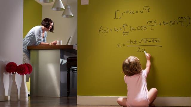 Ein Kleinkind schreibt mathematische Formeln auf die Tapete.