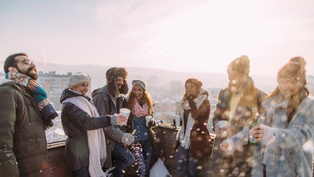 Freunde feiern in der Kälte draußen auf einer Dachterrasse