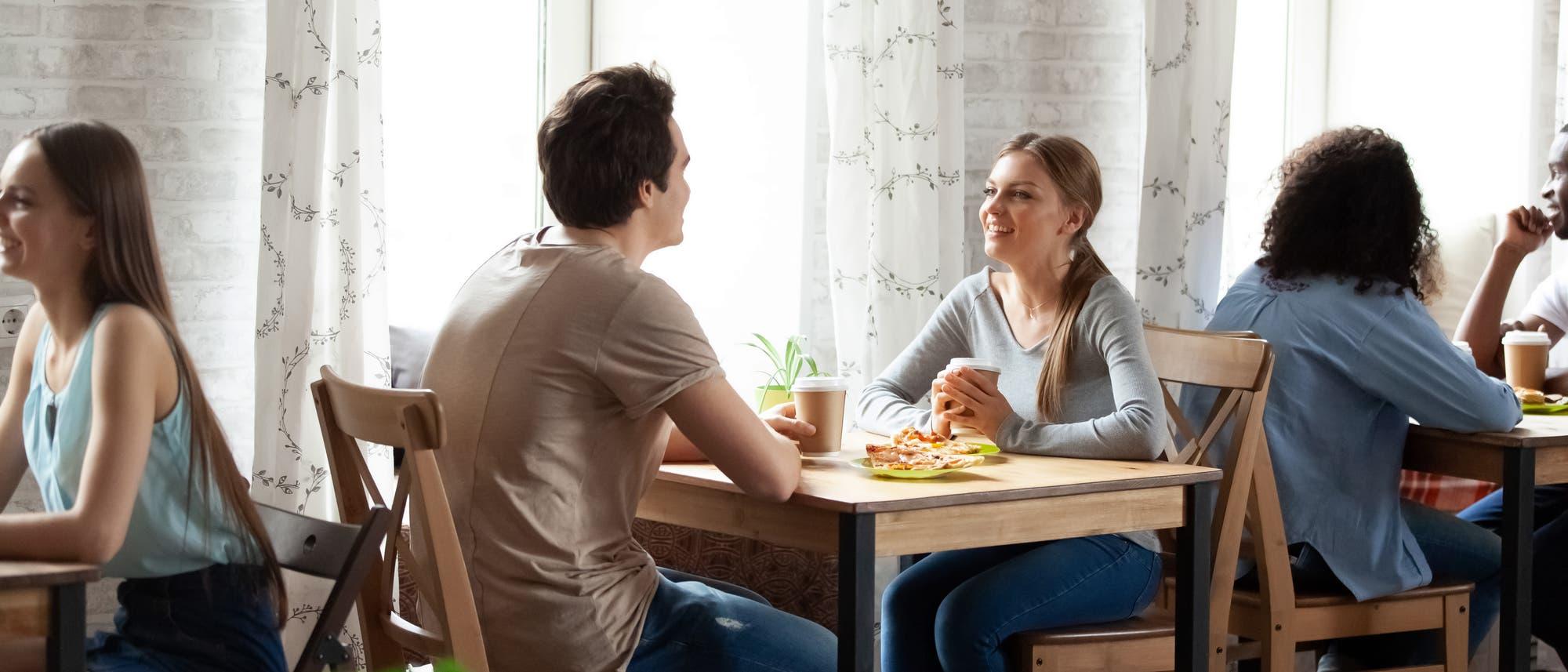 Mann und Frau sitzen im Café am Tisch und plaudern