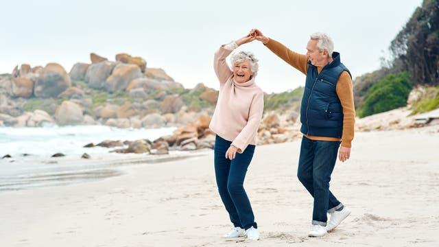 Älteres Paar tanzt am Strand