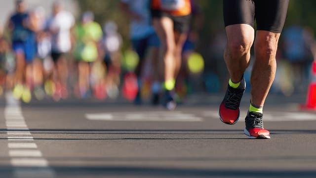 Blick auf die Beine von Marathonläufern während des Laufes.