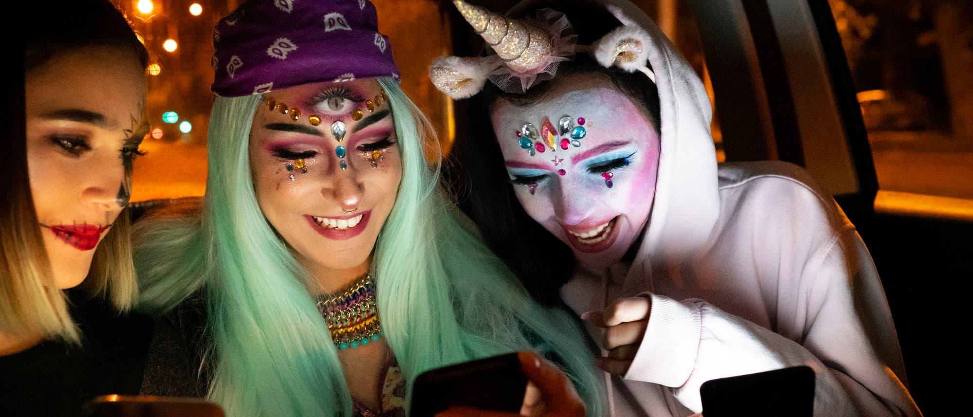 Zwei junge Frauen und ein Einhorn kommunizieren auf dem Weg zum Kostümball mit sich und ihren Smartphones