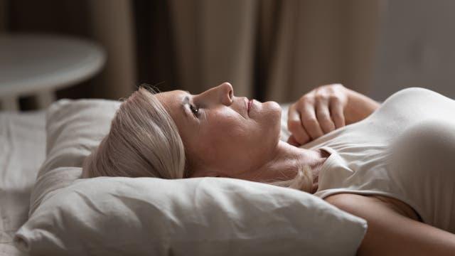 Eine Frau mittleren Alters liegt wach im Bett