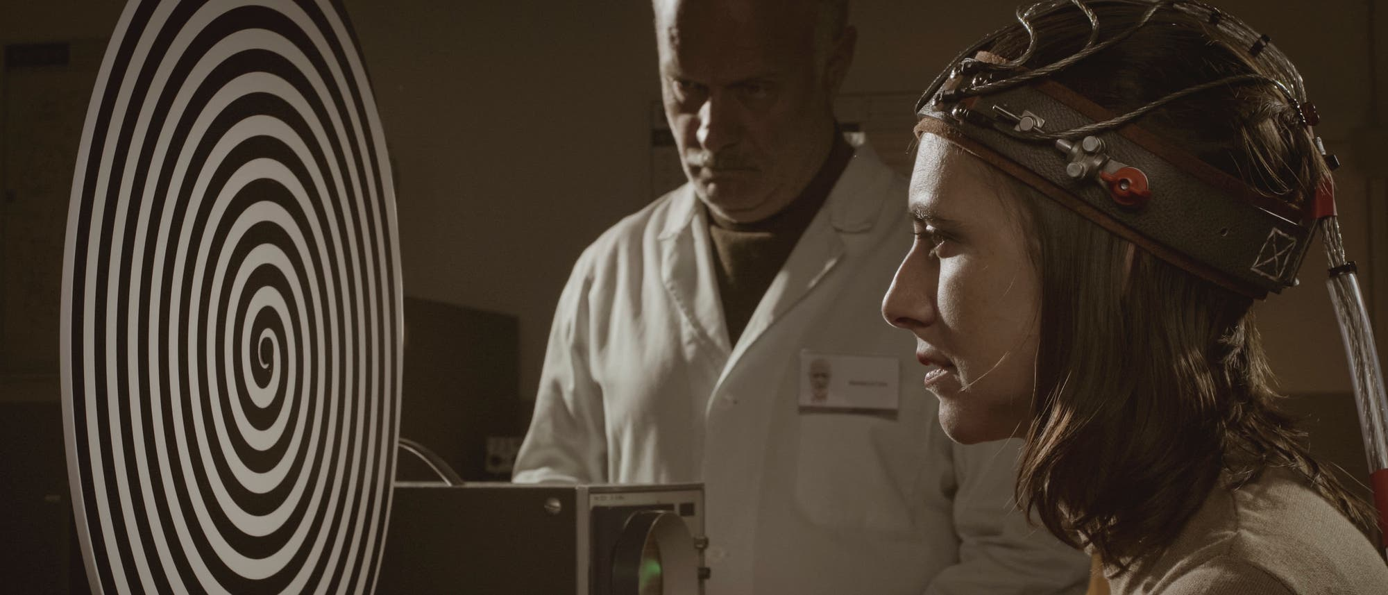 Frau mit Kabeln am Kopf schaut auf eine Spirale, beobachtet von einem Forscher