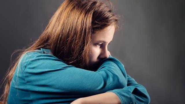 Eine junge Frau guckt traurig ins Leere