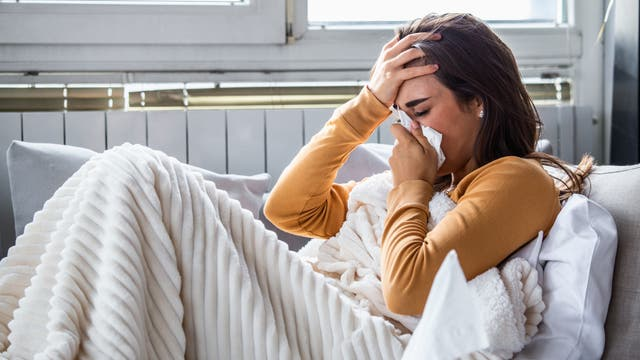 Eine Frau liegt, in eine Wolldecke gewickelt, auf ihrem Sofa. Aber sie schneuzt in ein Taschentuch, das heißt, sie ist erkältet und nicht einfach nur seit einem Jahr im Home Office.