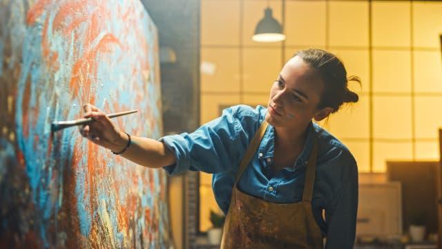 Junge Frau malt ein abstraktes Gemälde