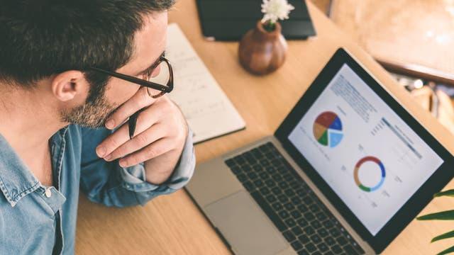 Ein Mann studiert Statistiken auf dem Computer