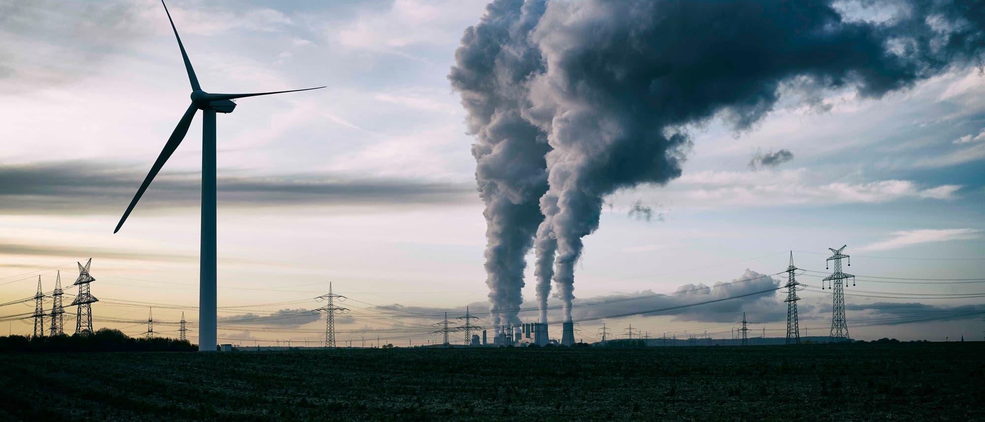 Windmühle neben rauchendem Kohlekraftwerk
