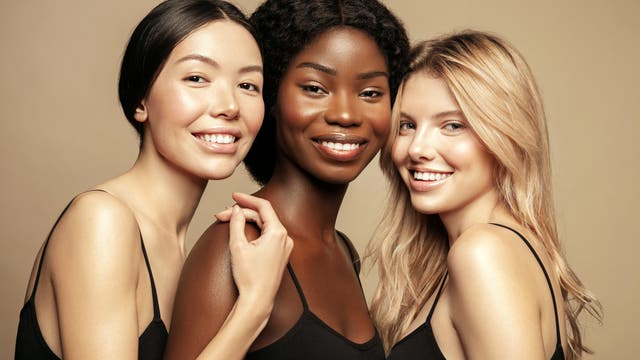 Lächelnde Frauengesichter dreier Ethnien