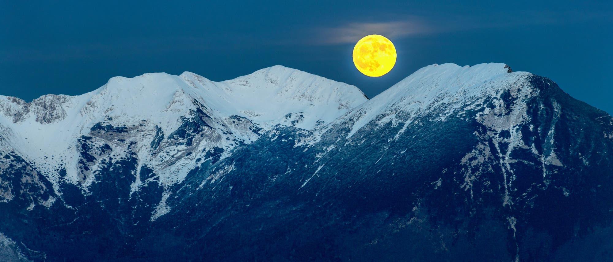 Der vollmond geht über einem schneebedeckten Berggrat auf.