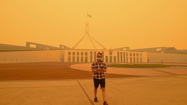 Ein Mann in Atemmaske und fragwürdig gemustertem Hemd steht vor dem australischen Parlament unter einem gelben Himmel.