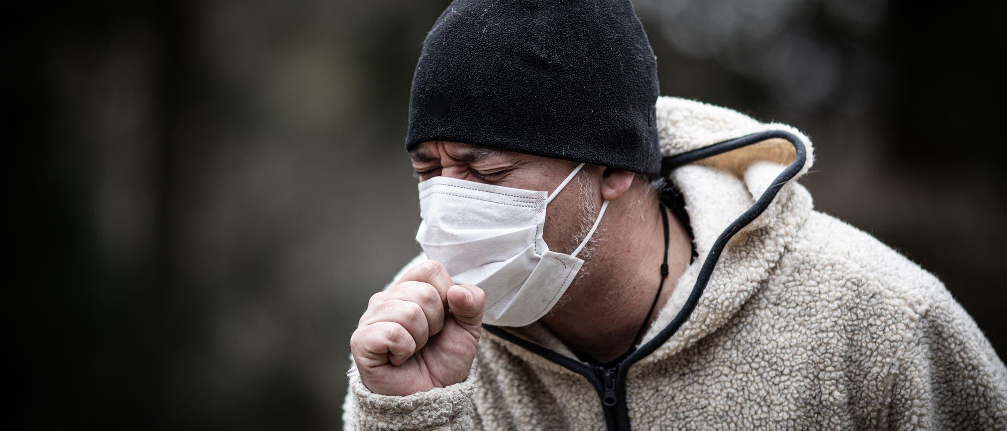 Hustender Mann mit Maske