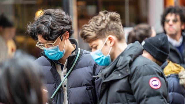 Zwei Junge Männer mit Mundschutz gucken auf ihre Handys, um den neuesten Spektrum-Artikel über das Coronavirus zu lesen.