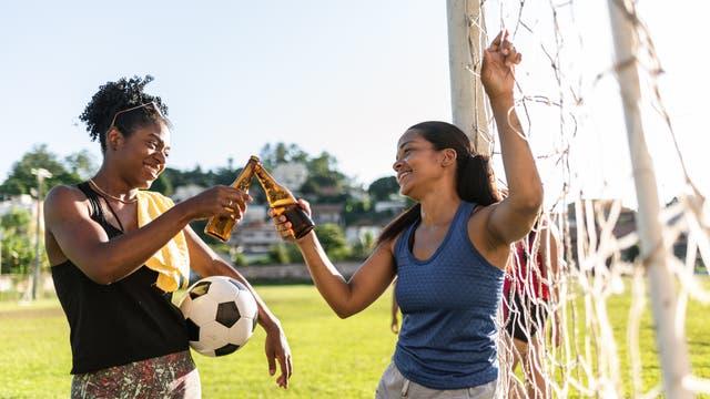 Zwei junge Fußballerinnen stoßen auf dem Feld mit einem Bier an.