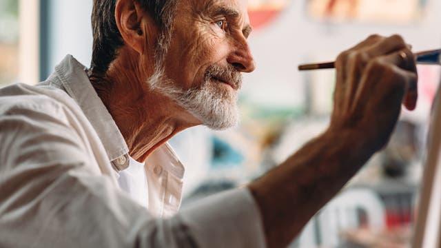 Mann an Staffelei beim Malen