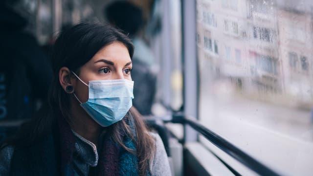 Frau mit Maske im Bus