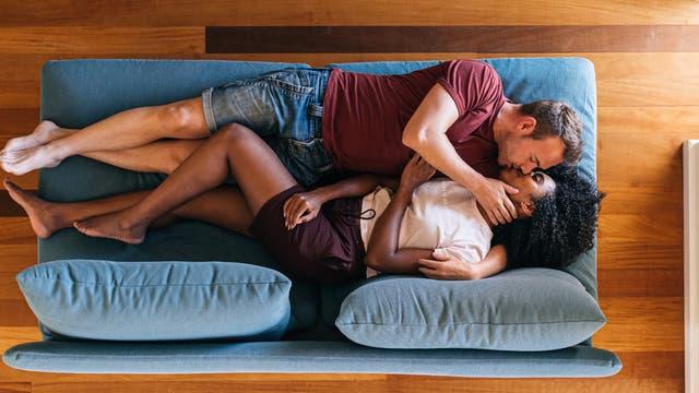 Junges Paar liegt auf der Couch und küsst sich