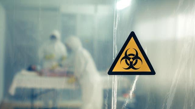 Hinter einer semitransparenten Plastikfolie beugen sich zwei Personan in Schutzausrüstung über eine liegende Person.