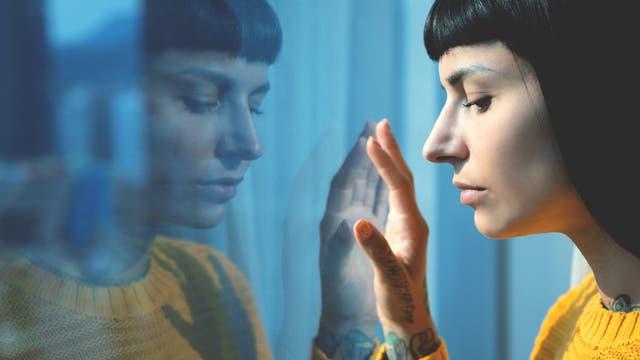 Frau spiegelt sich in Fenster