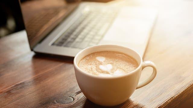 Ein Milchkaffee steht vor einem Laptop