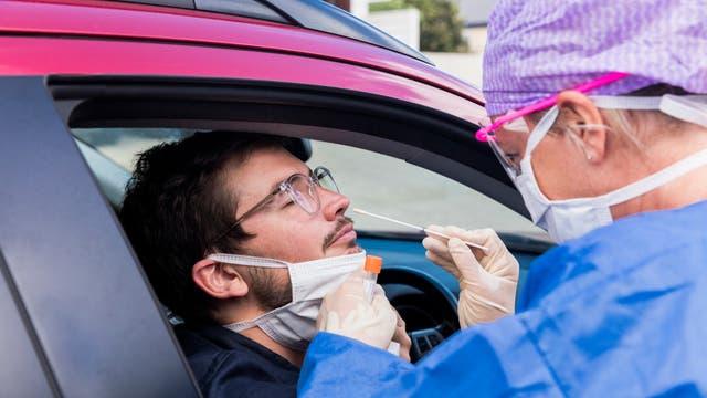 Ein Mediziner in Schutzkleidung nimmt einen Nasenabstrich von einem Autofahrer. Ein sehr guter Grund, kein Corona-Verdachtsfall zu werden ist übrigens, dass einem bei do einem Test das Stäbchen auf kompletter Länge durch die Nase bis in den Rachen gerammt wird.