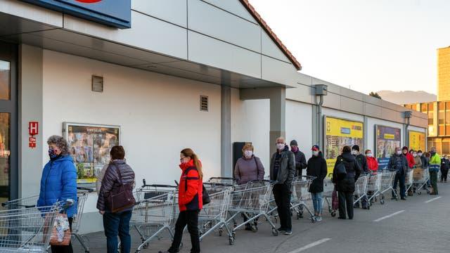 Menschen mit Gesichtsmasken und Einkaufswagen stehen Schlange am Eingang zum Supermarkt.