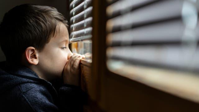 Ein Junge blickt niedergeschlagen aus dem Fenster.