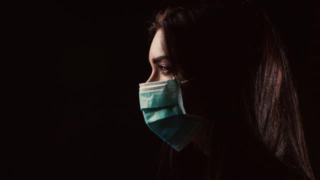Frau mit medizinischer Mund-Nase-Maske im Profil vor dunklem Hintergrund.