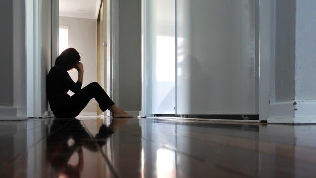 Eine Frau sitzt traurig auf dem Boden im Flur.