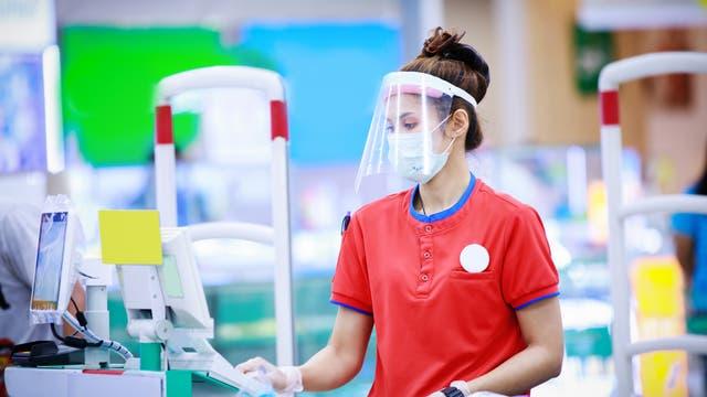 Verkäuferin im Supermarkt mit Maske und Visier