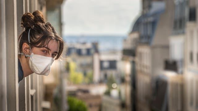 Frau schaut aus dem Fenster während des Lockdowns