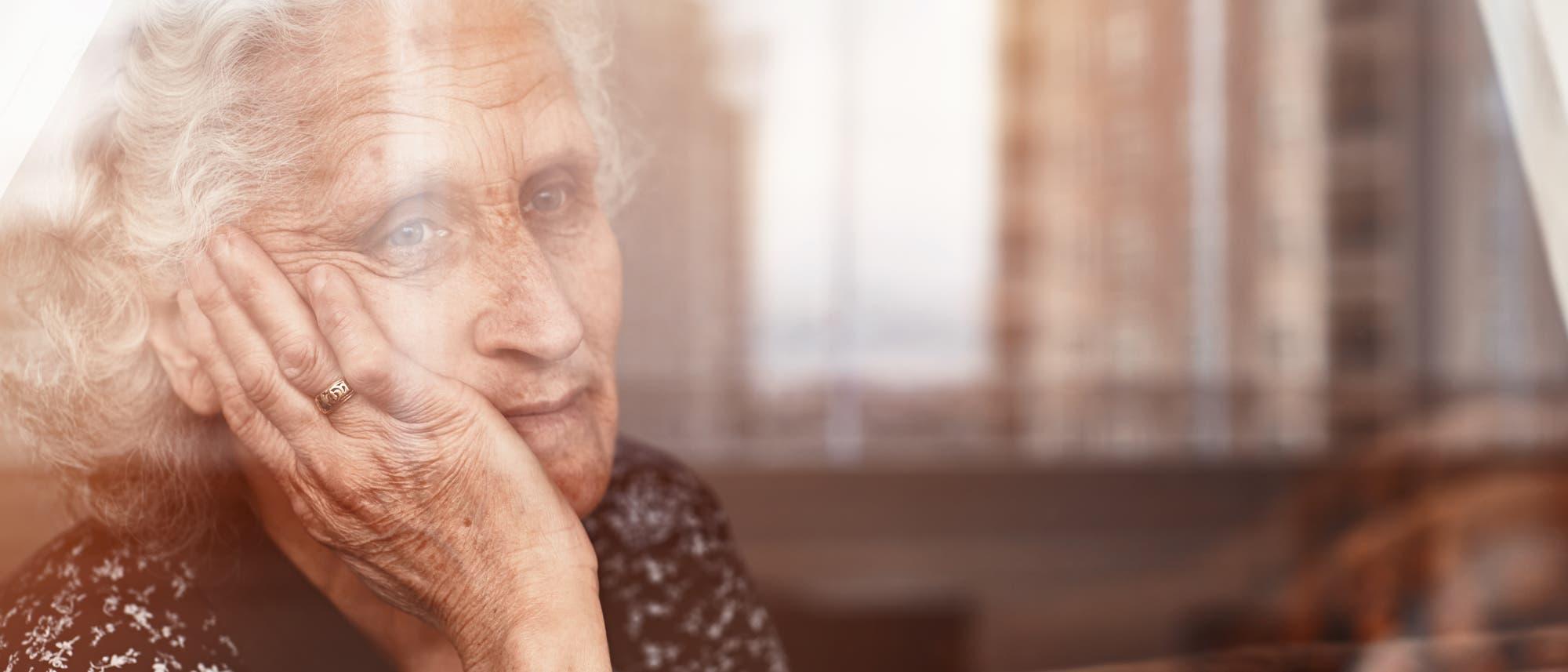 Eine ältere Frau blickt aus dem Fenster ihrer Wohnung.