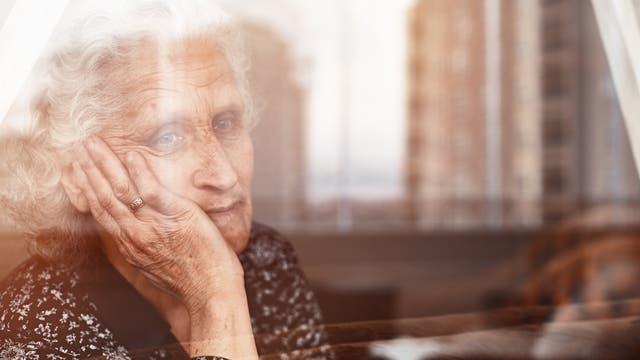Ältere Frau blickt aus dem Fenster